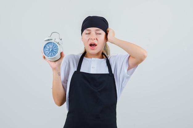 Giovane cameriera in uniforme e grembiule che tiene sveglia e che sembra smemorato