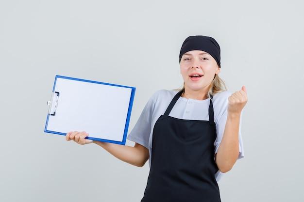 Giovane cameriera in uniforme e grembiule che tiene appunti e mostra il gesto del vincitore