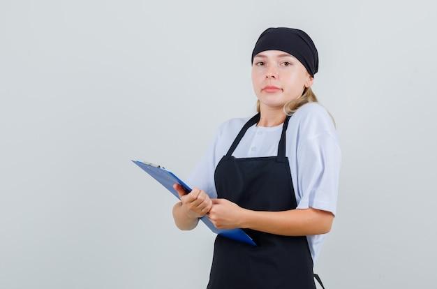 Giovane cameriera in uniforme e grembiule che tiene appunti