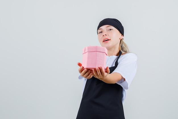 Giovane cameriera in uniforme e grembiule che tiene la scatola presente e sembra ottimista