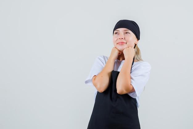 Giovane cameriera in uniforme e grembiule che tiene i pugni sul mento e sembra speranzosa