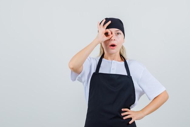Giovane cameriera in uniforme e grembiule che mostra il gesto giusto sull'occhio e sembra curiosa