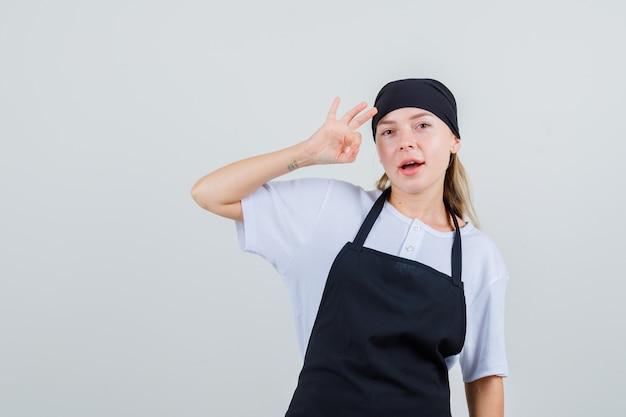 Giovane cameriera in uniforme e grembiule che mostra segno giusto e sembra soddisfatta