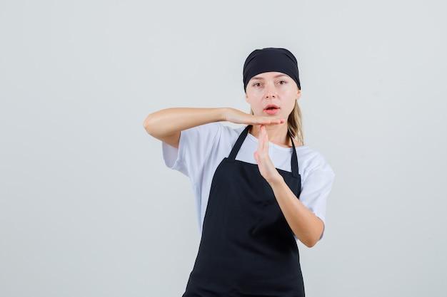 Giovane cameriera in uniforme e grembiule che mostra gesto di pausa di tempo
