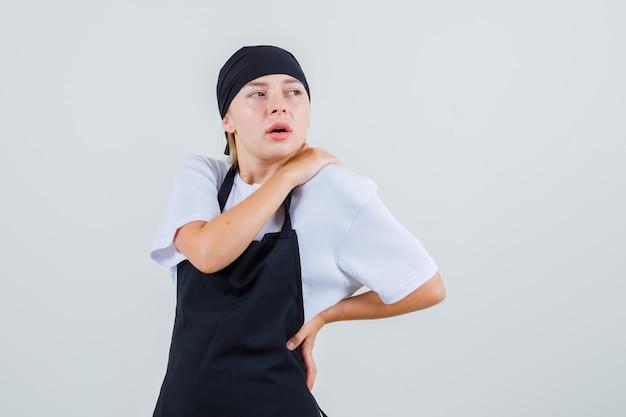 Giovane cameriera in uniforme e grembiule che soffre di mal di schiena e sembra stanca
