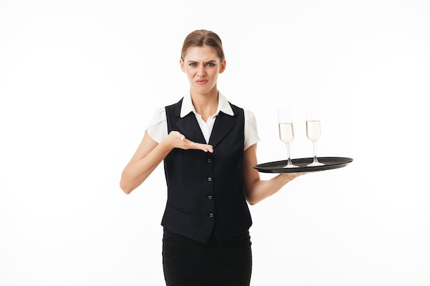 Young waitress in uniform holding tray with glasses sadly