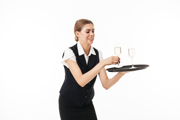 Young waitress in uniform trying to hold tray with glasses