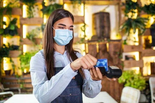 Молодая официантка в защитной маске делает оплату кредитной картой с помощью устройства для чтения карт