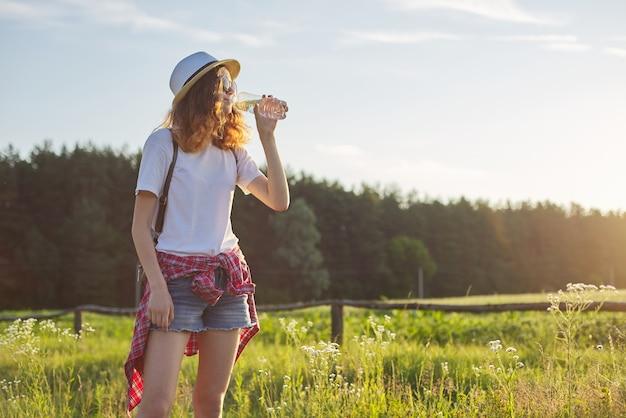 ボトルから水を飲む若い歩く十代の少女。背景の性質