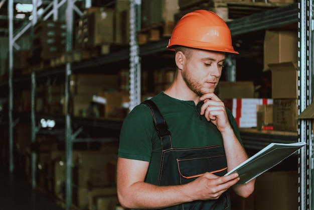 Young warehouse worker in hardhat with notebook