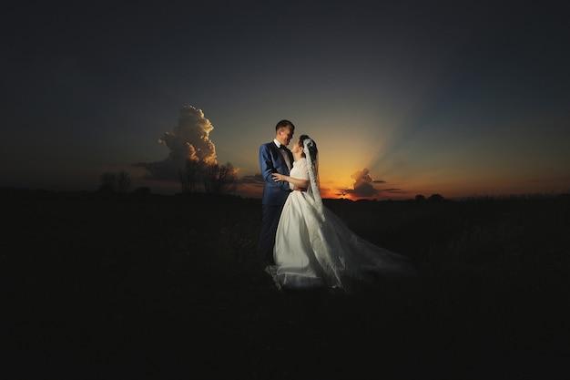 Молодая свадебная пара обнимается в поле в летний свадебный день на закате.