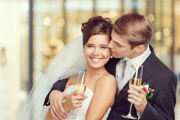 Молодая свадебная пара жених и невеста, держа бокалы для шампанского