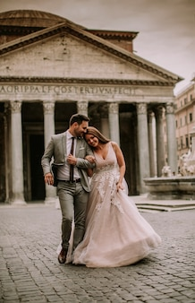 Young wedding couple by pantheon in rome, italy