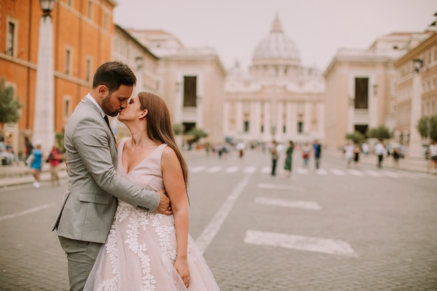Young wedding couple by saint peter cathedral in vatican