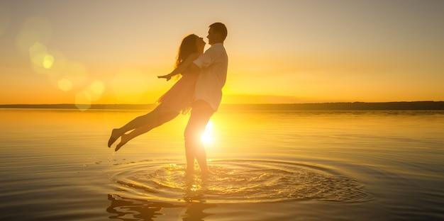 若い結婚式のカップルが夏のビーチで水に抱きしめています。海に沈む美しい夕日。太陽を背景にした2つのシルエット。ロマンチックなラブストーリー。新婚旅行で恋をしている男女。