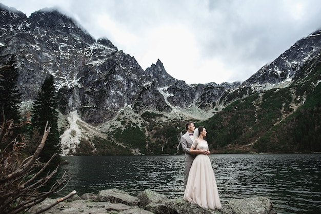 Young wedding couple posing on the shore of the lake morskie oko, poland, tatra