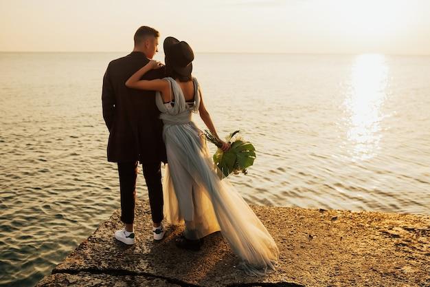 若い結婚式のカップルは、夕日を見ながら海のビーチに立っています。