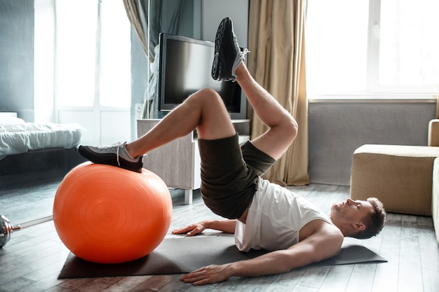 Young well-built man go in for sports in apartment. guy hold one foot on red fitness ball and reach another one to the top in air.