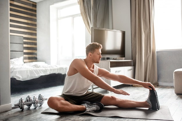 Young well-built man go in for sports in apartment. he sit on carimate and stretch body. guy reach end of toe with hand. concentrated muscular man.