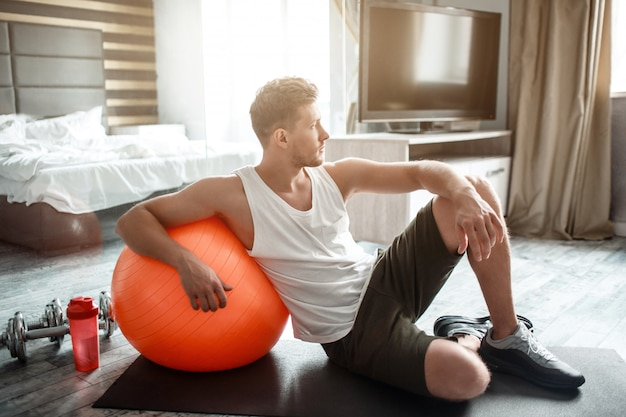 Young well-built man leans to big fitness ball and look at window