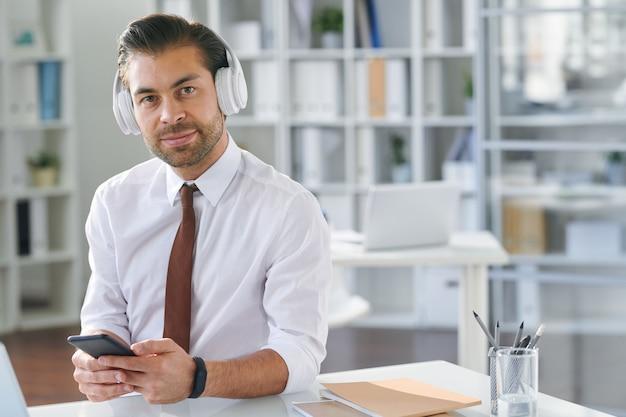 Молодой хорошо одетый бизнесмен со смартфоном, слушающий музыку из плейлиста на рабочем месте