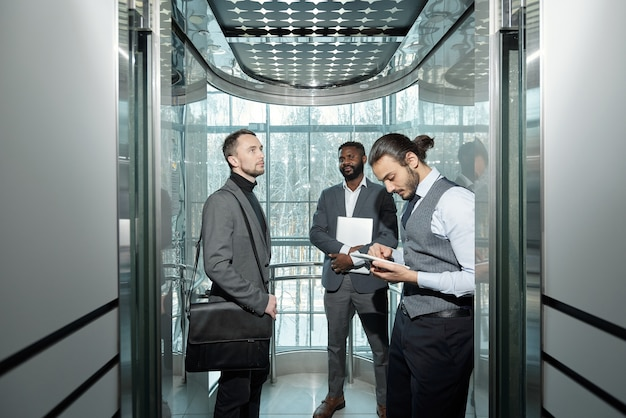 Young well-dressed male entrepreneur using tablet in elevator of modern business center among his colleagues