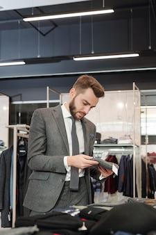 Молодой хорошо одетый мужчина просматривает новую коллекцию в современном бутике и выбирает новую вязаную шапку