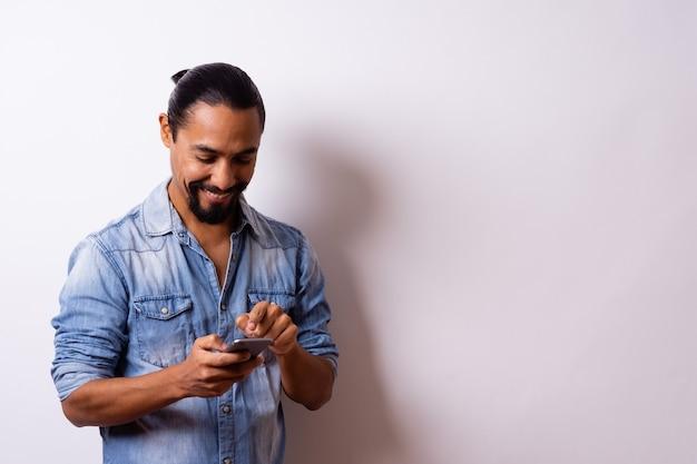 ひげを生やした手入れの行き届いた若い現代ラテン系アメリカ人は満足そうに笑い、タブレットに指を向けます。ビジネスコンセプト。