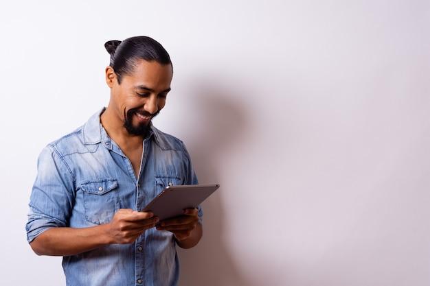 ひげを生やした若い手入れの行き届いたモダンなラテン系アメリカ人は、購入するためにタブレットを見て満足そうに笑い、彼の側または4分の3にいて、右側にスペースを残しています。