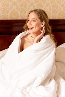 Young well-slept waking up in bed, smiling and holding blanket
