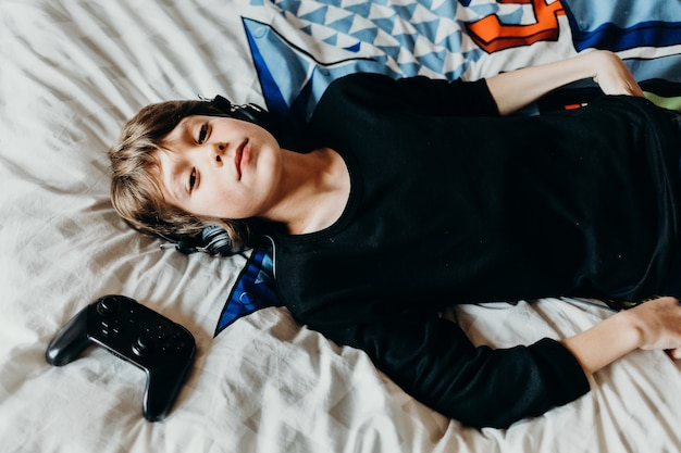 Young white boy laying on his bad with a wireless controller