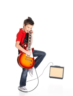 A young white boy sings and plays on the electric guitar with bright emotions, isolatade on white
