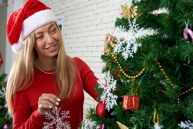 Молодая белая кавказская женщина в шляпе сата-клаус с улыбкой украшает рождество / сосну в помещении для веселых и счастливых новогодних праздников