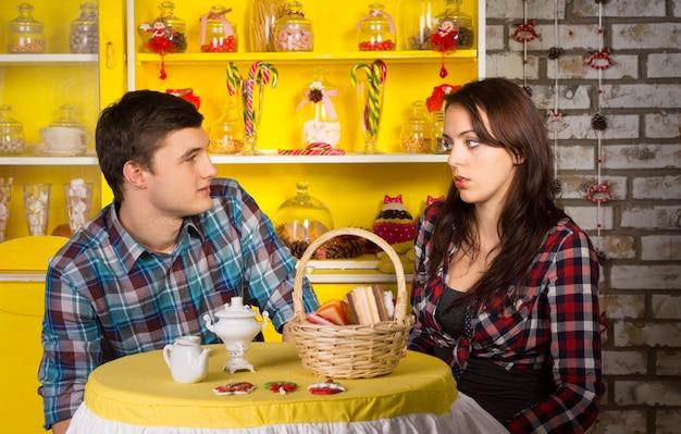 デートをしながらスナックバーでお互いを見ている市松模様のシャツを着た若い白人カップル。