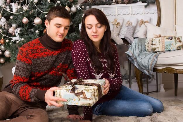 カジュアルな服を着て床に座って、飾られたクリスマスツリーの前に1つのギフトボックスを保持している若い白人カップル。