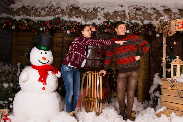 Young white couple in trendy winter fashion near indoor white snowman looking at right frame inside the house with plenty attractive christmas decorations.
