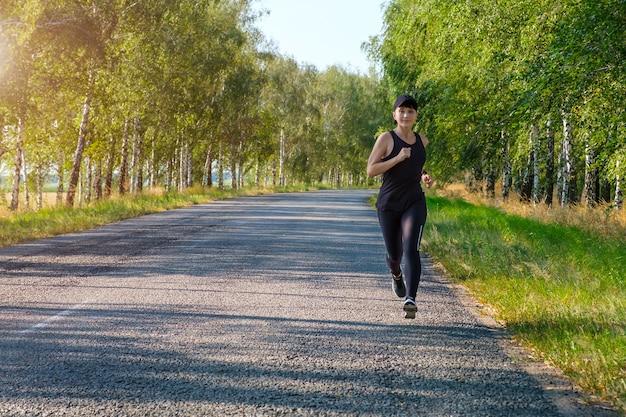 国の道路側に沿って走る若い白いフィットネス女性