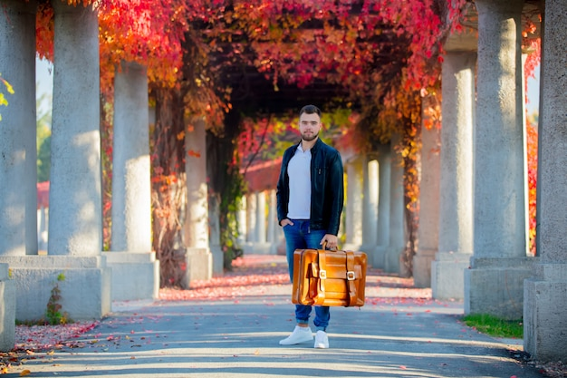 Young white guy with suitcase on red grape alley