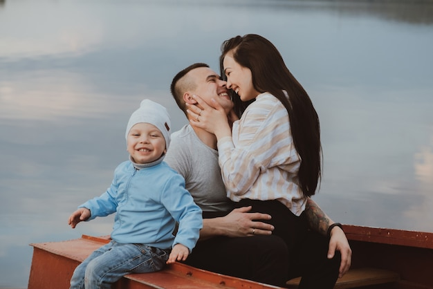 Young white happy family with their son sit in a boat by the water in the summer