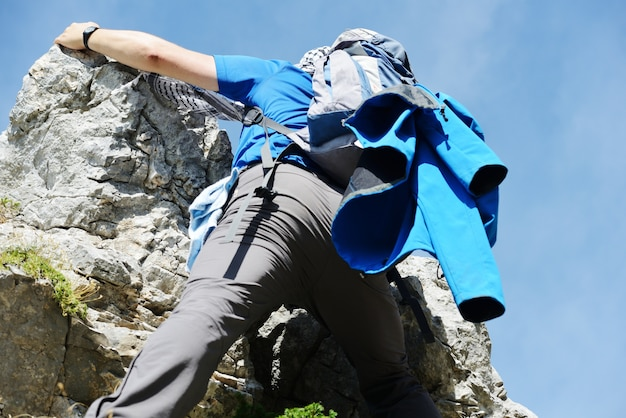 Young white man climbing a steep wall in mountain, rock-climb extreme sport