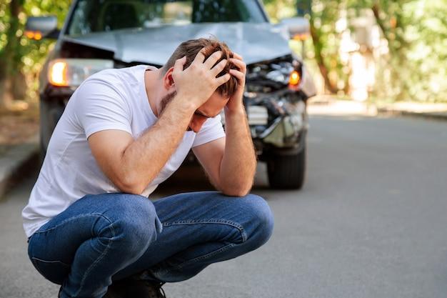 Молодой белый мужчина водитель в автокатастрофе и держится за голову возле разбитой машины на дороге после автомобильной аварии. кавказский мужчина держит в руках травму головы после аварии