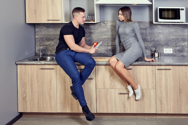 Young white man flirts in kitchen of  university dormitory with slender caucasian woman.