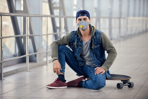 Young white man in hoody sitting on a skateboard on the street with a medical face mask on.