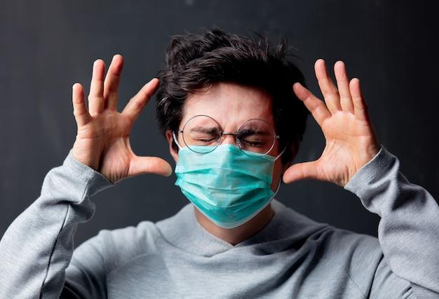 Молодой белый человек в очках и защитной маске с головной болью