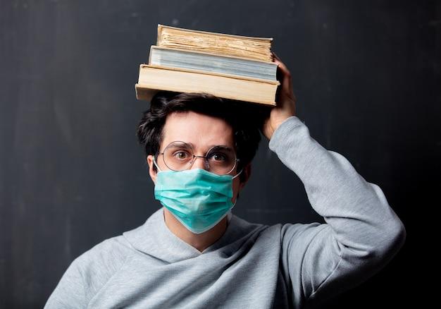 Молодой белый человек в очках и защитная маска с книгами