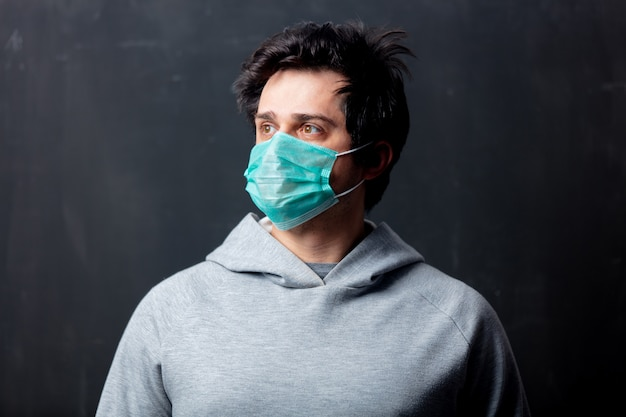 Young white man in protective mask on dark background
