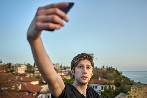 Молодой белый мужчина фотографирует себя на фоне старого города в анталии с помощью смартфона