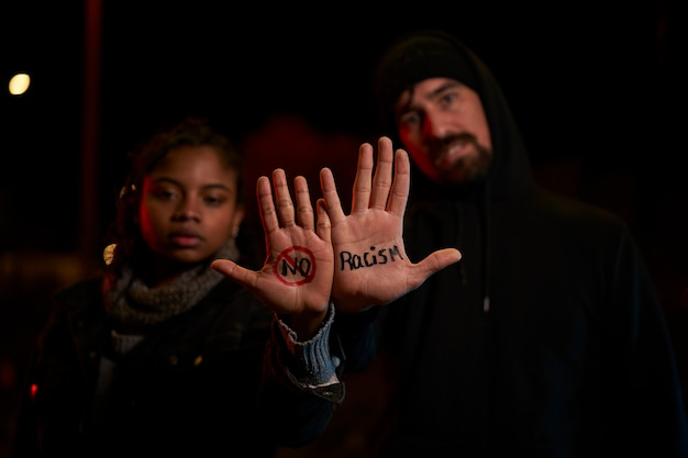 A young white man and a young black woman displaying a handwritten message against racism.