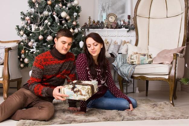 若い白人のパートナー、男が持っている現在の箱を見て、クリスマスツリーとエレガントな大きな椅子の前の床のカーペットに座っています。