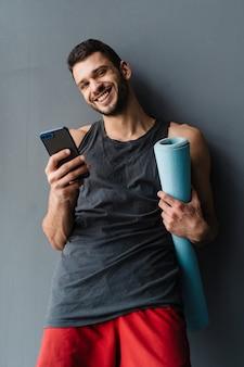 실내에서 매트를 들고 서 있는 동안 휴대폰을 사용하는 젊은 백인 스포츠맨